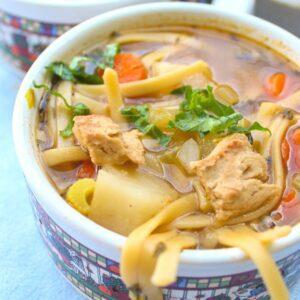 Close up of vegetarian chicken noodle soup in a large mug.